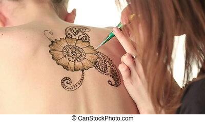 Art of mehndi. Master draws on girl's back