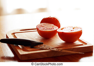 tomato on cutting board - slices of tomatoes on a wooden...