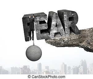 Man shackled by ball hanging fear word edge cliff cityscape...