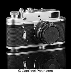Old retro camera isolated on black background