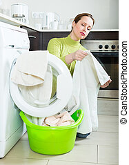Woman with washing machine - unhappy woman in green doing...