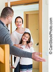 Couple with girl at doorway - Happy man standing at doorway...