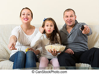 Family watching TV show - Parents and cute girl watching TV...