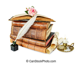 Old books, burning candle in candlestick, white feather in...