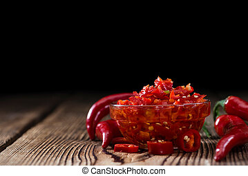 Preserved red Chilis (close-up shot) on wooden background