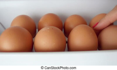 Women hand Open fridge filled and taking a fresh eggs from refrigerator
