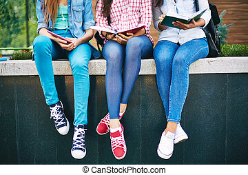Girls reading - Modern teen girls reading outside
