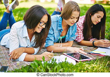 Schoolwork outside - Modern teen girls doing schoolwork...