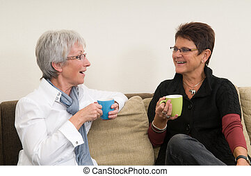 Coffee Chat - Two senior women drinking coffee, chatting and...