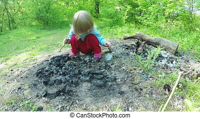 Baby on fireplace - Girl child playing coals on fire site