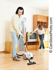middle-aged couple doing housework in home