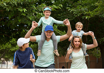 Parents with kids outdoor - Happy cheerful parents with.