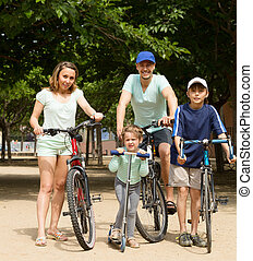 family of four walking in park with bicycles