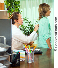 Doctor with teenager patient - Friendly female doctor with...