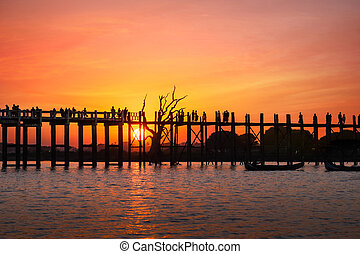 Silhouettes at U Bein teak bridge at sunset Myanmar Burma -...