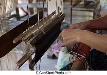 Woman weaving silk at manual loom. Laos - Woman weaving silk...