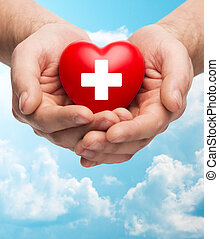 male hands holding red heart with white cross - family...