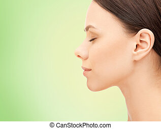 beautiful young woman face over green background - health,...
