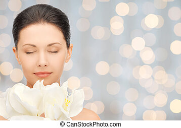 beautiful woman smelling flowers with closed eyes - beauty,...