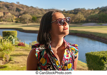 Young woman in sunglasses enjoying summer breeze at beach -...