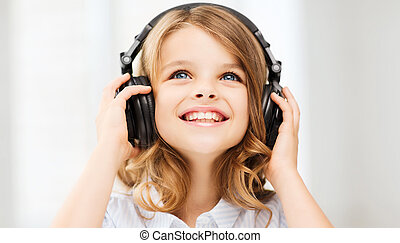 little girl with headphones at home - home, technology and...