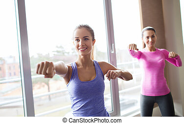 group of happy women working out in gym - fitness, sport,...