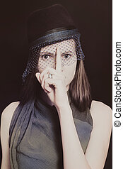 Retro portrait of a beautiful young woman in a hat with a veil