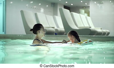 Swimming Lesson - Side view of mother teaching her little...
