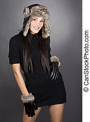 winter woman - pretty brunette wearing winter outfit on grey...