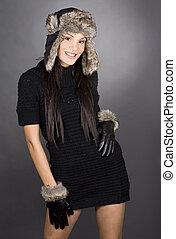 winter woman - pretty brunette wearing winter outfit on grey...