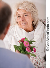 Man giving wife daisy bouquet - Senior man giving ill wife...