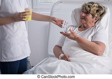 Caring about bedridden woman - Young nurse caring about...