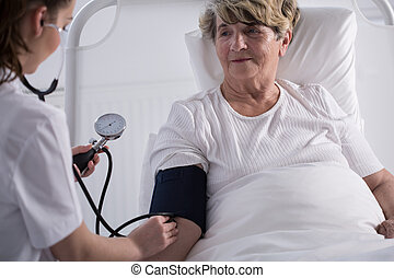 Nurse measuring blood pressure in hospital ward