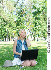 Happy woman downloading music outdoors with laptop and...