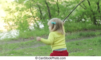 Child with stick picnic - Girl child in nature is played...
