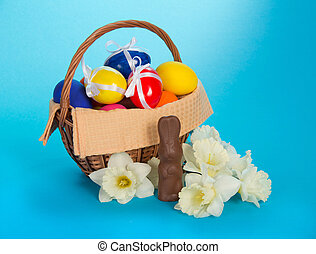 Chocolate rabbit, white narcissuses and a basket with eggs,...