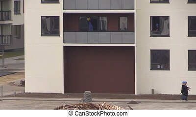 clean flat house window - workers with helmets clean window...