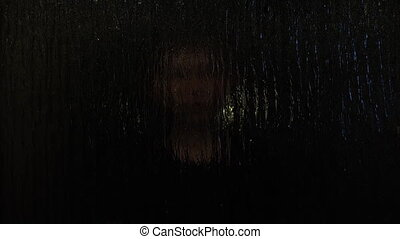 child playing hide and seek behind frosted glass