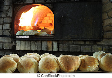 Bakery - Baked bread in front of a brick oven
