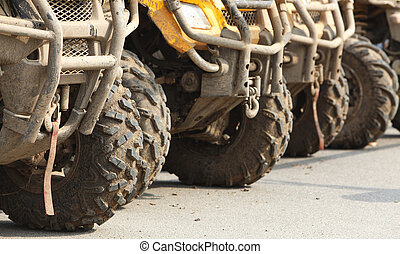 Trucks - Low angle veiw of the front part of a row of ATVs.