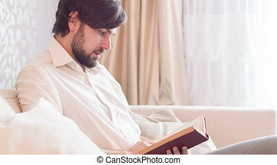 Young man reading book - Good time. Young handsome man...