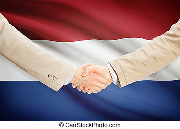 Businessmen handshake with flag on background - Netherlands...
