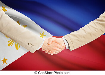 Businessmen handshake with flag on background - Philippines...