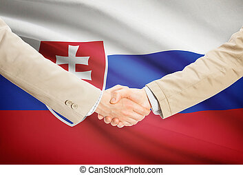 Businessmen handshake with flag on background - Slovakia -...