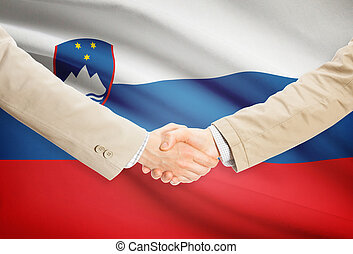 Businessmen handshake with flag on background - Slovenia -...