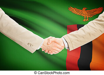 Businessmen handshake with flag on background - Zambia -...