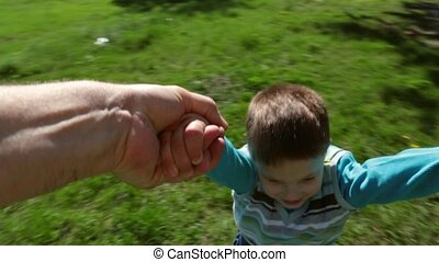Father spinning his happy son on green lawn in park, slow...