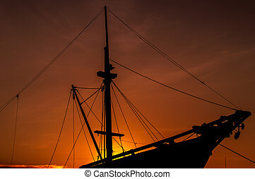 wooden ship - silhouette wooden ship at sunset