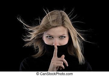 blonde girl in a black turtleneck making a hush gesture -...