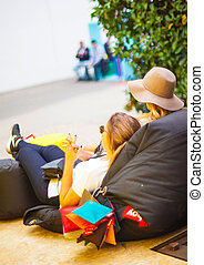 Two young girls lie down on pouf - MILAN, ITALY - APRIL 16:...